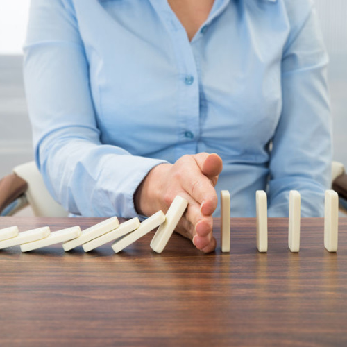 38811890 - close-up of businesswoman stopping the effect of domino with hand at desk